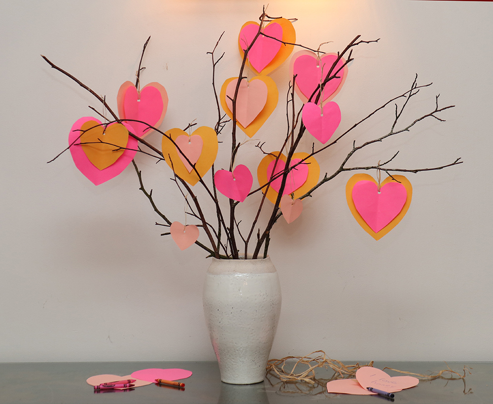 A Valentine tree made of twigs in a vase with pink paper hearts